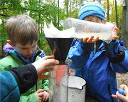Kinder schütten Wasser in einen Zylinder