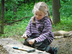 Kind bearbeitet einen Stein